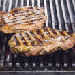 Cooking beef steak on grill in restaurant — Stok Fotoğraf #25418703