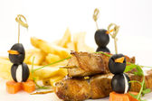French fries and kebabs of chicken — Stock Photo