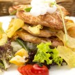 Salad with chicken and potatoes on a white plate in a restaurant — Foto Stock