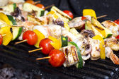 Skewers of seafood grilling — Stock Photo