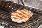 Cooking beef steak on a grill — Stock Photo