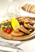 Chicken wings are grilled on a wooden platter — Stock Photo