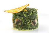 Fried spinach decorated with a slice of orange — Stock Photo
