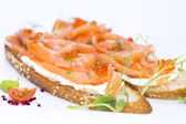 Sandwiches with salmon caviar and greens adorned — Stock Photo