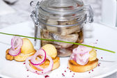 Pickled herring in a glass jar with potato canapes — Stock Photo