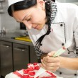 Pastry chef decorates a cake — Stock Photo #40150295