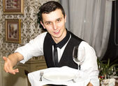 Waiter with a tray of food in the restaurant hall — Stok fotoğraf