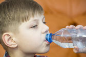 Boy drinks water from a plastic bottle — Stock Photo