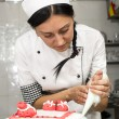 Pastry chef decorates a cake — Stock Photo