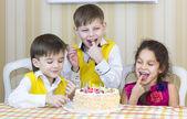 Kids have fun eating birthday cake — Stock Photo