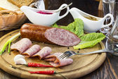 Sausage on a wooden plate — Stock Photo