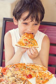 Boy eating pizza — Stock Photo