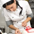 Pastry chef decorates a cake — Stock Photo #48496319