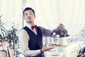 Waiter with a tray of food — Stock Photo