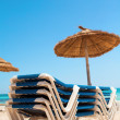 Deck chairs and parasol on the beach — Stock Photo