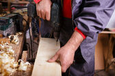 Carpenter at work with a drill in joinery — Stock Photo