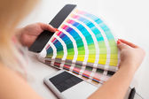 Graphic designer working on a digital tablet and with pantone pa — Stock Photo