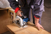 Hands carpenter working with circular saw — Stock Photo