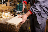 Carpenter at work with electric planer joinery — Stock Photo