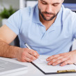 Young businessman in blue polo shirt signs a contract — Stock Photo