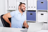 Young businessman has backache at work with a laptop — Stock Photo