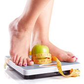 A pair of female feet standing on a bathroom scale with green ap — Stock Photo