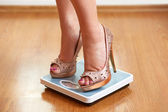 Female feet in golden stilettos on a weight scale — Stock Photo