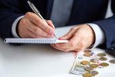 Mano di uomo d'affari che tiene una penna scrivendo sul blocco note — Foto Stock