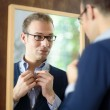 Young man dressing up and looking at mirror — Stock Photo #11433581