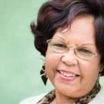 Portrait of happy elderly black lady with eyeglasses smiling — Stock Photo
