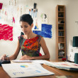 Hispanic woman doing budget in fashion designer atelier - Foto Stock
