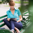 Hispanic woman with digital tablet pc on bench — Stock Photo