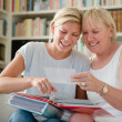 Foto Stock: Mother and daughter looking at pictures in photo album
