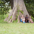Three happy female friends sitting near big tree - Stockfoto