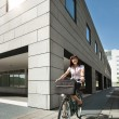 Woman riding bicycle and going to work - Stockfoto