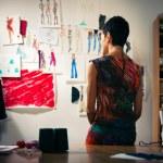 Female fashion designer contemplating drawings in studio — Stock Photo #13886932