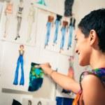 diseñador de moda femenina contemplando los dibujos de estudio — Foto de Stock