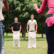 Men playing sack race with girlfriends cheering — Stock Photo