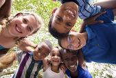 Dzieci, obejmując w krąg wokół aparatu i uśmiechając się — Zdjęcie stockowe