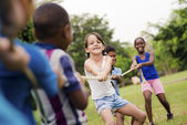 Happy school children playing tug of war with rope in park — Stok fotoğraf