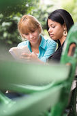 College students studying on textbook in park — Stock Photo
