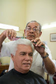 Old barber cutting hair to client in barber shop — Stock Photo