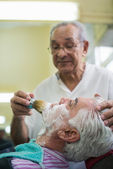 Senior man at work as barber shaving customer — Stock Photo