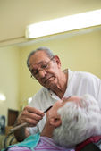 Elderly barber with razor shaving client in barber shop — Stock Photo