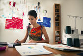 Hispanic woman doing budget in fashion designer atelier — Foto Stock