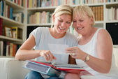 Mother and daughter looking at pictures in photo album — Stockfoto