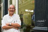 Retrato de viejo barbero sonriendo en peluquería — Foto de Stock