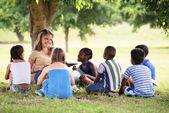 Niños y educación, profesora de lectura del libro a los jóvenes estudiantes — Foto de Stock