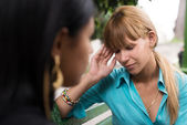 Woman having headache while talking with friend — Stock Photo