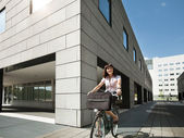 Woman riding bicycle and going to work — Stock Photo